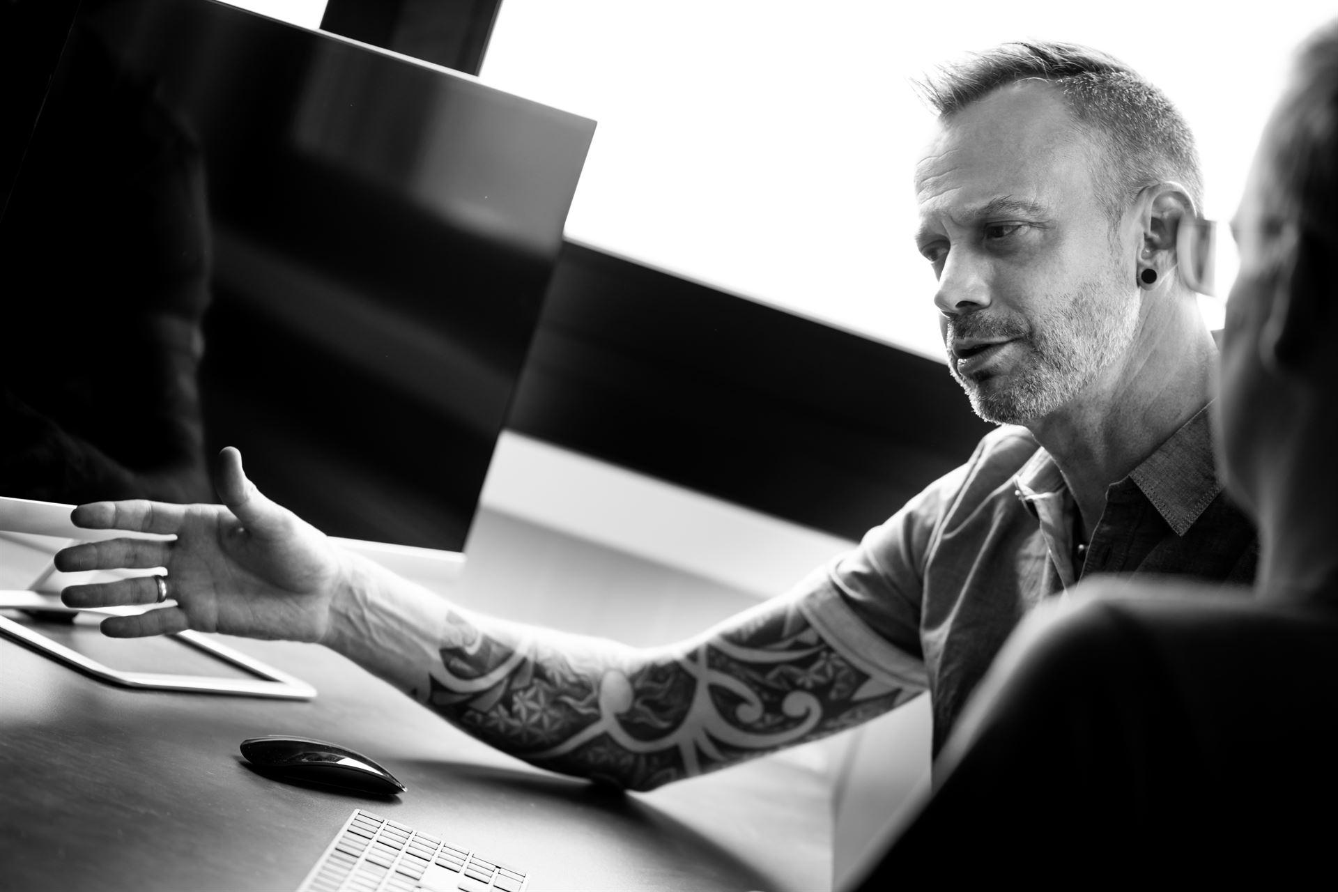hils IT - Hils erklärt Kunde, Bildschirm im Hintergrund